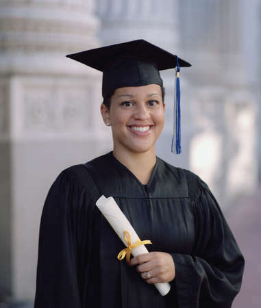 attainment: Young female graduate standing outdoors holding a diploma smiling LANG_EVOIMAGES