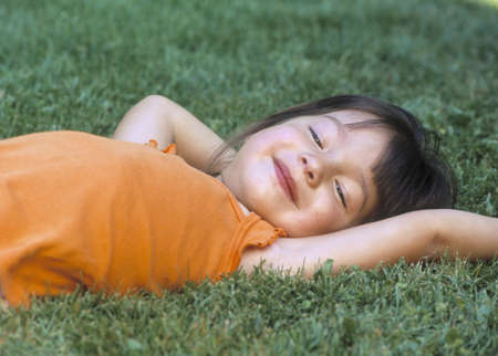 informant: Young girl lying on a lawn smiling