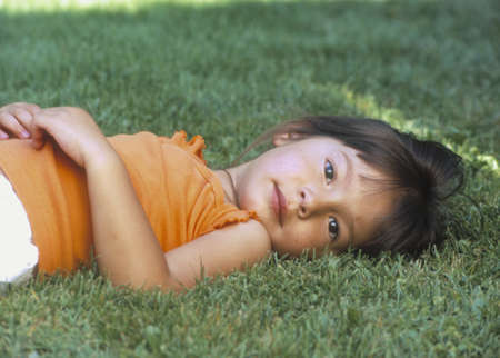 informant: Young girl lying on a lawn looking at camera LANG_EVOIMAGES
