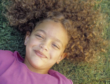 informant: Young girl lying on a lawn looking at camera grinning LANG_EVOIMAGES