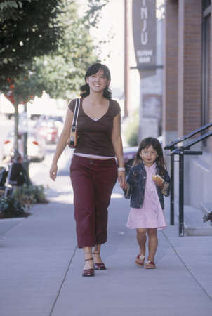 Portrait of a mother walking with a young girl holding hands Stock Photo - 16044217