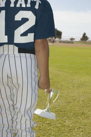 airs: Rear view of a young boy walking holding a trophy cup