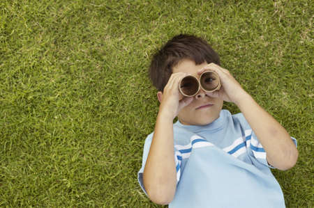 Young boy lying on a lawn looking up with cardboard tubes over his eyes Stock Photo - 16044228