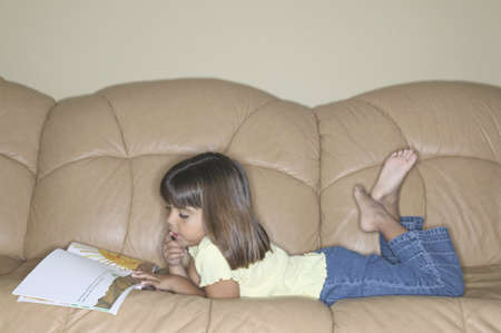 erudition: Young girl lying on a couch reading a book
