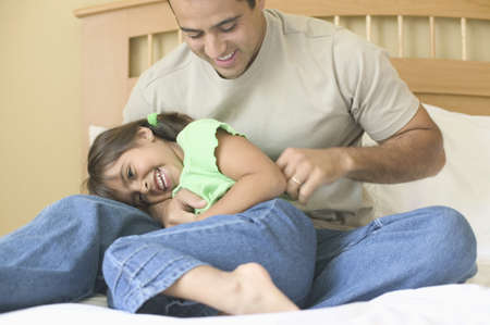 restfulness: Young man playing with a young girl on a bed
