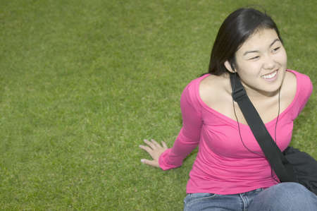 knee bend: Young woman sitting on a lawn smiling LANG_EVOIMAGES