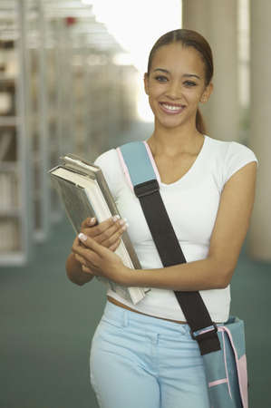 Portrait of a teenage girl standing in a library holding books smiling