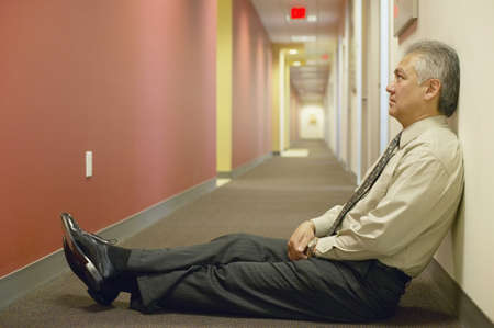 restfulness: Side profile of an adult businessman sitting on the floor in a corridor