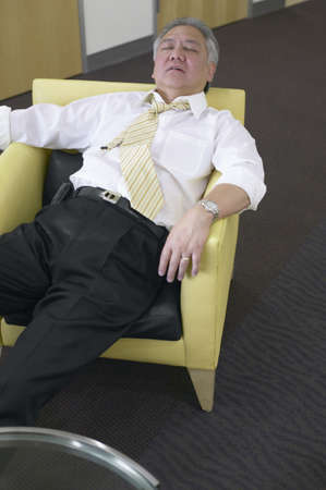 restfulness: Mature businessman relaxing in a chair