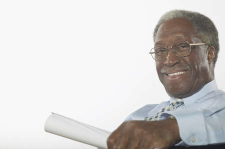 effrontery: Portrait of an elderly man sitting holding a sheet of paper LANG_EVOIMAGES