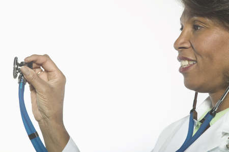 mid adult female: Portrait of mid adult female doctor standing holding a stethoscope