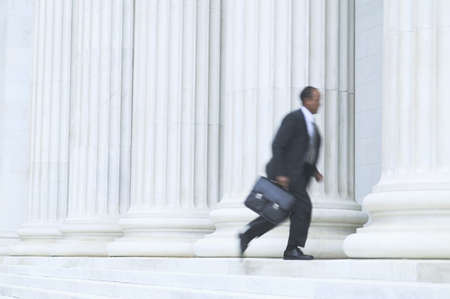 hurrying: Side profile of a mid adult businessman running into a building holding a briefcase LANG_EVOIMAGES