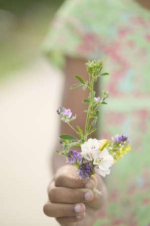 Teenager girl standing holding flowers