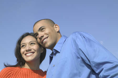 ebullient: Low angle view of a Young couple standing together smiling
