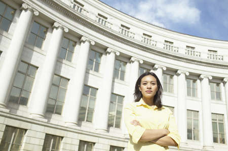 way of behaving: Low angle view of a young woman standing with her arms folded
