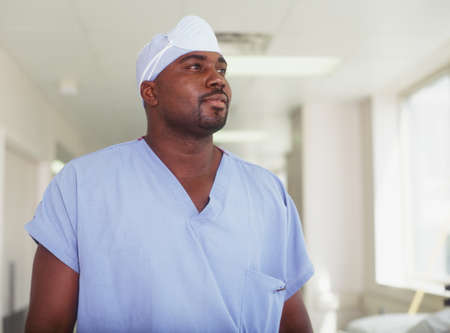 effrontery: Male surgeon standing in a hospital corridor