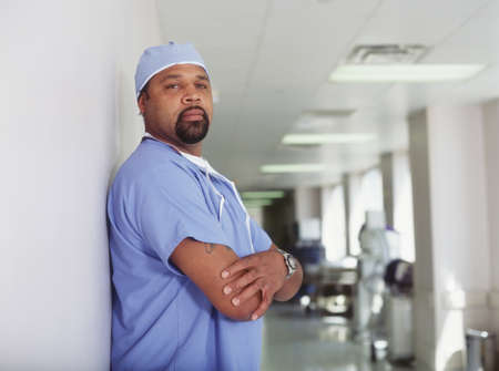effrontery: Male nurse standing in a hospital corridor LANG_EVOIMAGES