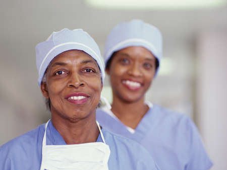effrontery: Two female nurses standing in a hospital corridor smiling LANG_EVOIMAGES