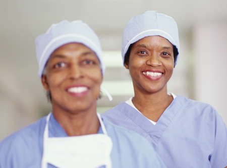 certitude: Two female nurses standing in a hospital corridor smiling LANG_EVOIMAGES
