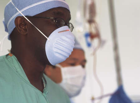 two persons only: Two male doctors wearing full scrubs in an operating theatre LANG_EVOIMAGES