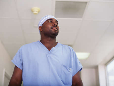 Low angle view of a surgeon standing in a hospital corridor LANG_EVOIMAGES