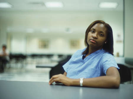 way of behaving: Portrait of a female nurse sitting at a table LANG_EVOIMAGES