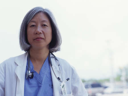 effrontery: Close-up of a doctor standing outdoors with a stethoscope around her neck LANG_EVOIMAGES