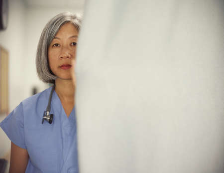 effrontery: Portrait of a female doctor standing in a hospital room