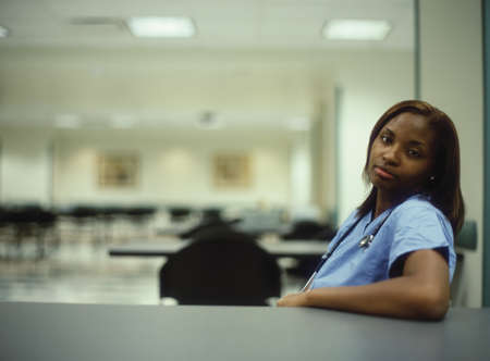 Female nurse relaxing at the hospital cafeteria