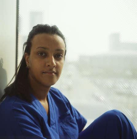 Female nurse sitting by a window Stock Photo - 16044395