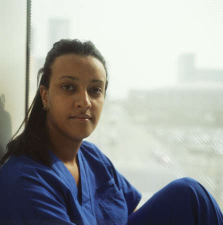 effrontery: Female nurse sitting by a window LANG_EVOIMAGES