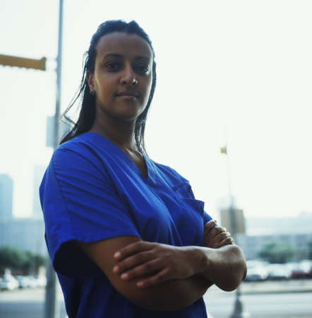 effrontery: Portrait of a female nurse standing with arms folded LANG_EVOIMAGES