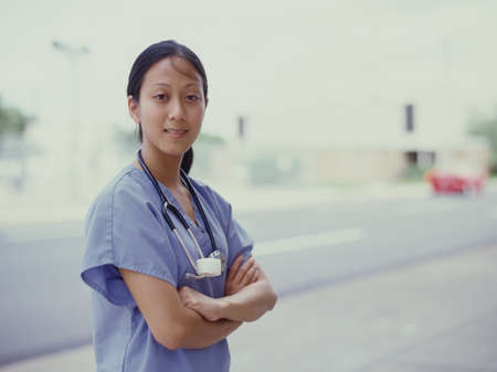 effrontery: Portrait of a female nurse standing outdoors