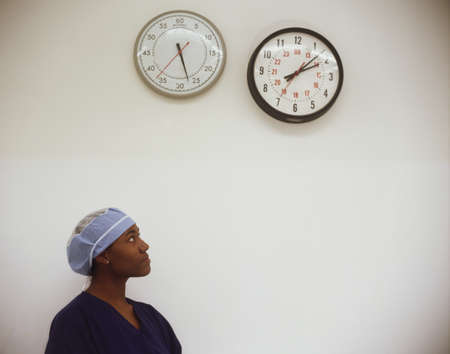 clock: Female nurse looking at a clock on a wall LANG_EVOIMAGES