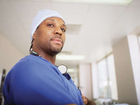 effrontery: An ICU male nurse standing in a hospital corridor LANG_EVOIMAGES
