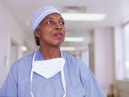 effrontery: Female nurse in full scrubs standing in a hospital corridor