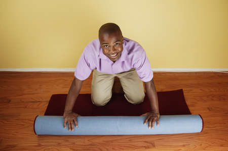 Young man rolling up a carpet