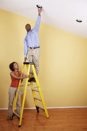 Young man standing on a ladder with a young woman standing beside him