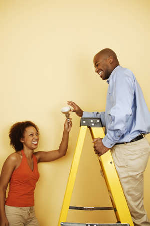 Young woman holding a light bulb smiling at a young man standing on a ladder Stock Photo - 16044435
