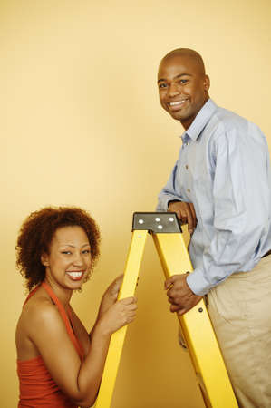 largesse: Side profile of a young couple standing on a ladder LANG_EVOIMAGES