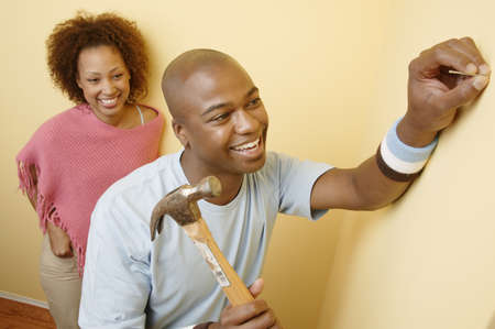 Young man holding a hammer and a nail with a young woman standing behind him Stock Photo - 16044439