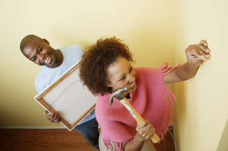 Young woman holding a hammer and a nail with a young man standing behind her Stock Photo - 16044440