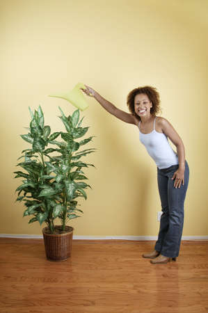 Portrait of a young woman watering a potted plant Stock Photo - 16044444