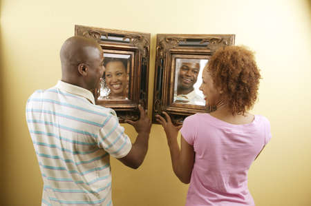 Rear view of a young couple holding framed mirrors