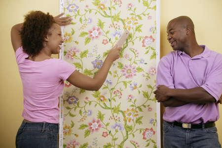 seres vivos: Pareja joven poniendo papel pintado en una pared LANG_EVOIMAGES
