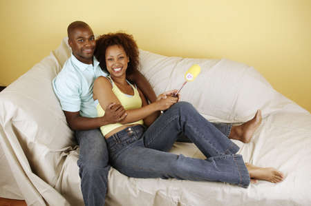 ebullient: Portrait of a young couple sitting on a covered couch