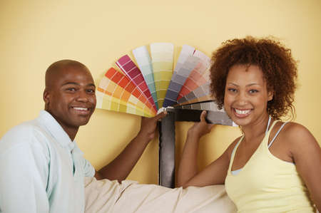 Portrait of a young couple holding color swatches Reklamní fotografie