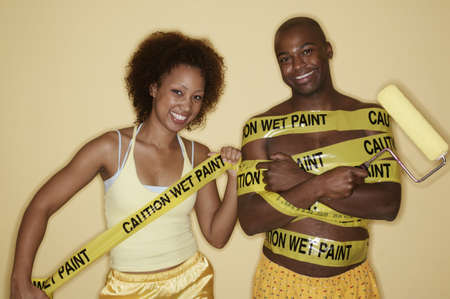 ebullient: Portrait of a young couple holding a paint roller and wrapped in yellow tape