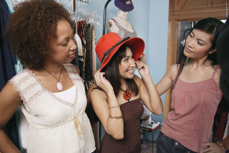 recourse: Three young women trying a hat in a department store LANG_EVOIMAGES