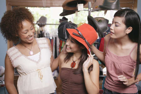 ebullient: Three young women trying a hat in a department store LANG_EVOIMAGES